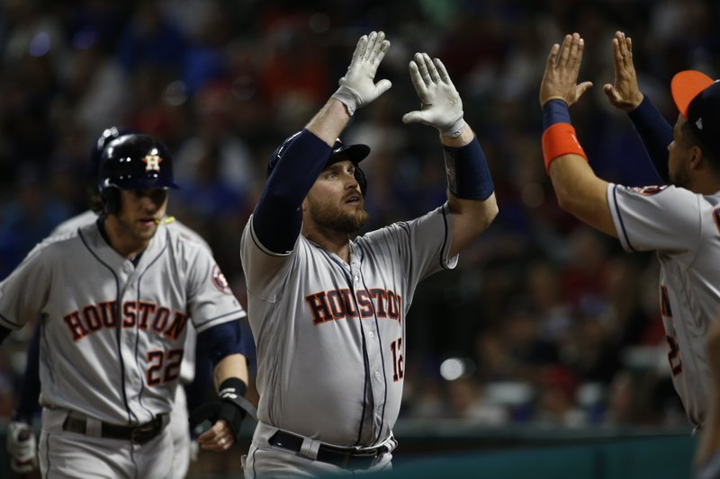 Houston Astros' Max Stassi (12) celebrates with teammates after hitting a two-run home run against the Texas Rangers as Josch Roddick, on left, is near during the fifth inning of a baseball game Saturday, April 20, 2019, in Arlington, Texas. (AP Photo/Mike Stone)