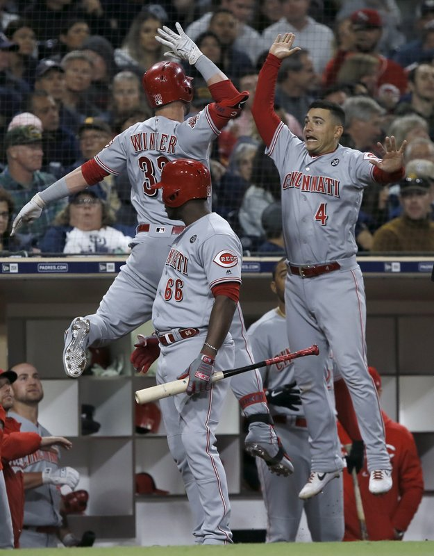 Cincinnati Reds' Jesse Winker, left, celebrates in a leap with Jose Iglesias, right, after hitting a solo home run as Yasiel Puig, center, watches, during the seventh inning of a baseball game against the San Diego Padres in San Diego, Saturday, April 20, 2019. (AP Photo/Alex Gallardo)