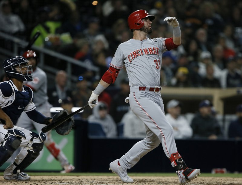 Cincinnati Reds' Jesse Winker, right, follows through to hit a solo home run with San Diego Padres catcher Francisco Mejia watching during the seventh inning of a baseball game in San Diego, Saturday, April 20, 2019. (AP Photo/Alex Gallardo)