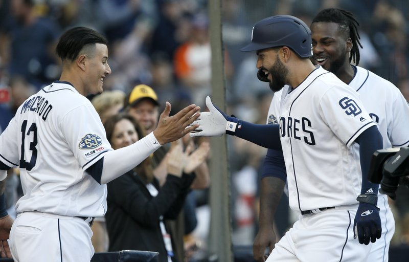 San Diego Padres' Eric Hosmer, second from right, celebrates with Manny Machado, left, and Franmil Reyes, right, after hitting a solo home run against the Cincinnati Reds during the second inning of a baseball game in San Diego, Saturday, April 20, 2019. (AP Photo/Alex Gallardo)