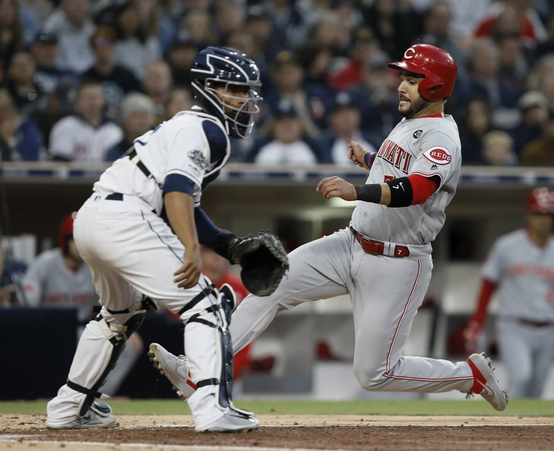 Cincinnati Reds' Eugenio Suarez, right, beats the throw to San Diego Padres catcher Francisco Mejia, left, to score on a sacrifice fly hit by Yasiel Puig during the fifth inning of a baseball game in San Diego, Saturday, April 20, 2019. (AP Photo/Alex Gallardo)