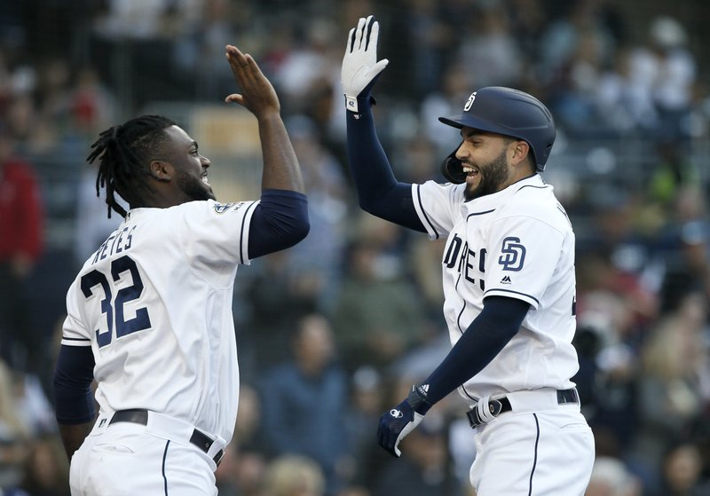 San Diego Padres' Eric Hosmer, right, celebrates with Franmil Reyes, left, after hitting a solo home run against the Cincinnati Reds during the second inning of a baseball game in San Diego, Saturday, April 20, 2019. (AP Photo/Alex Gallardo)