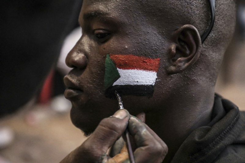 A man's face is painted as Sudanese protesters chant slogans during a rally outside the army headquarters in Sudan's capital Khartoum on Saturday, April 20, 2019. (AP Photo)