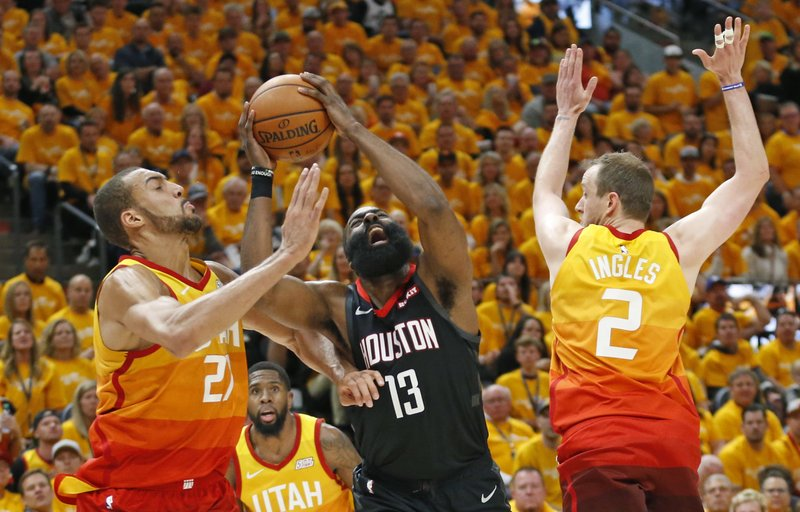 Utah Jazz's Rudy Gobert, left, and Joe Ingles (2) defend against Houston Rockets guard James Harden (13) in the first half during an NBA basketball game Saturday, April 20, 2019, in Salt Lake City. (AP Photo/Rick Bowmer)