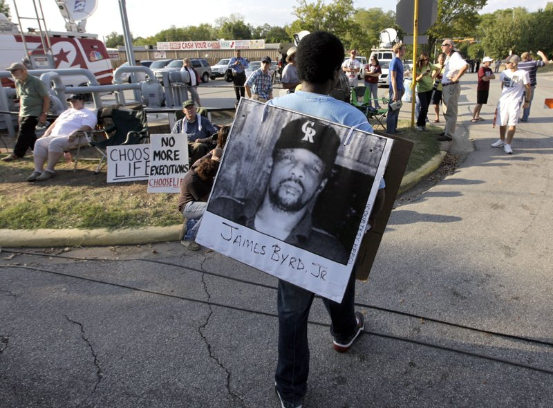 FILE - In this Sept. 21, 2011, file photo, Ricky Jason wears a photograph of James Byrd Jr. outside the Texas Department of Criminal Justice Huntsville Unit before the execution of Lawrence Russell Brewer in Huntsville, Texas. (AP Photo/David J. Phillip, File)