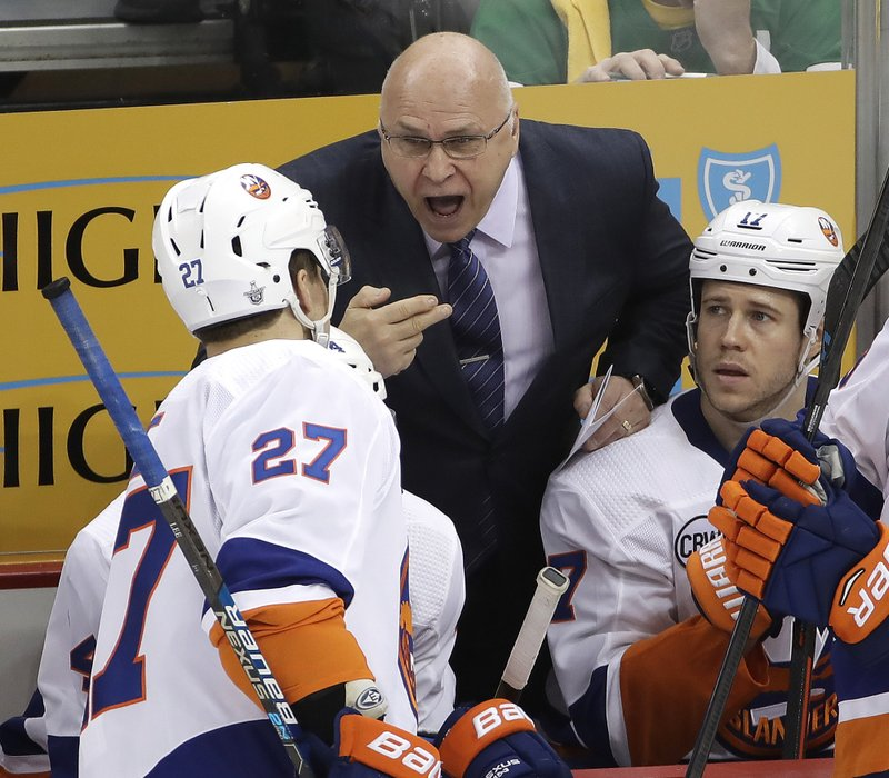 New York Islanders head coach Barry Trotz, center, gives instructions to Anders Lee (27) during the third period in Game 3 of an NHL first-round hockey playoff series against the Pittsburgh Penguins in Pittsburgh, Sunday, April 14, 2019. (AP Photo/Gene J. Puskar)