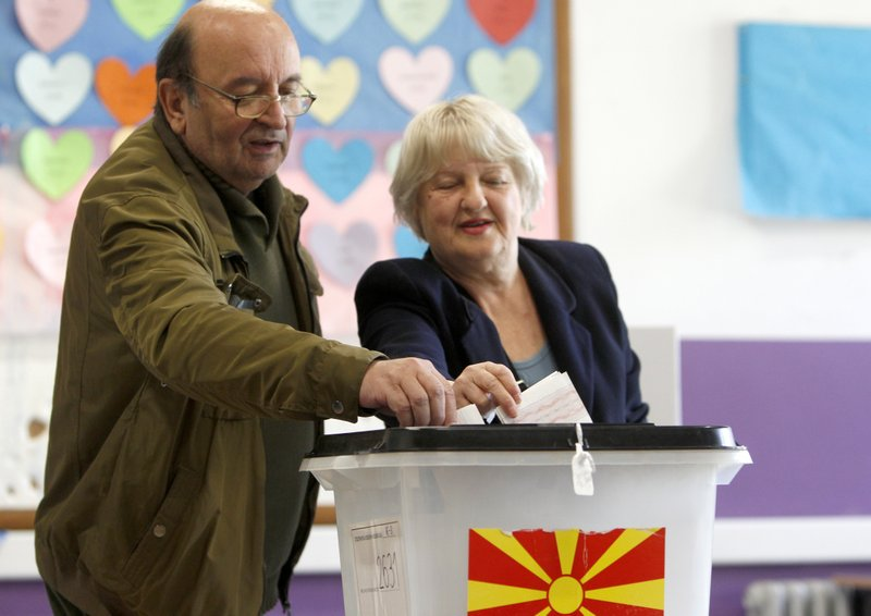 A couple cast their ballots for the presidential election at a polling station in Skopje, North Macedonia, Sunday, April 21, 2019. (AP Photo/Boris Grdanoski)