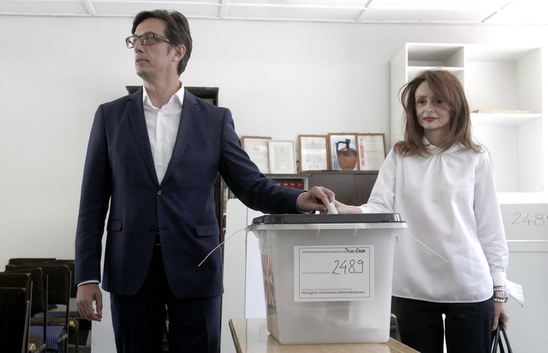 Stevo Pendarovski, left, a presidential candidate of the ruling coalition led by the Social Democrats and his wife Elizabeth Gjorgievska cast their ballots for the presidential elections at a polling station in Skopje, North Macedonia, Sunday, April 21, 2019. (AP Photo/Boris Grdanoski)