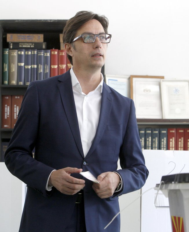 Stevo Pendarovski, a presidential candidate of the ruling coalition led by the Social Democrats, holds his ballot before voting for the presidential elections at a polling station in Skopje, North Macedonia, Sunday, April 21, 2019. (AP Photo/Boris Grdanoski)