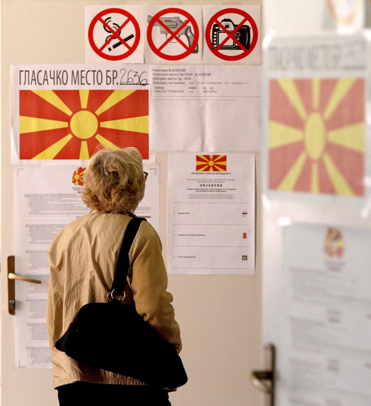 A woman checks lists before voting for the presidential election at a polling station in Skopje, North Macedonia, Sunday, April 21, 2019. (AP Photo/Boris Grdanoski)