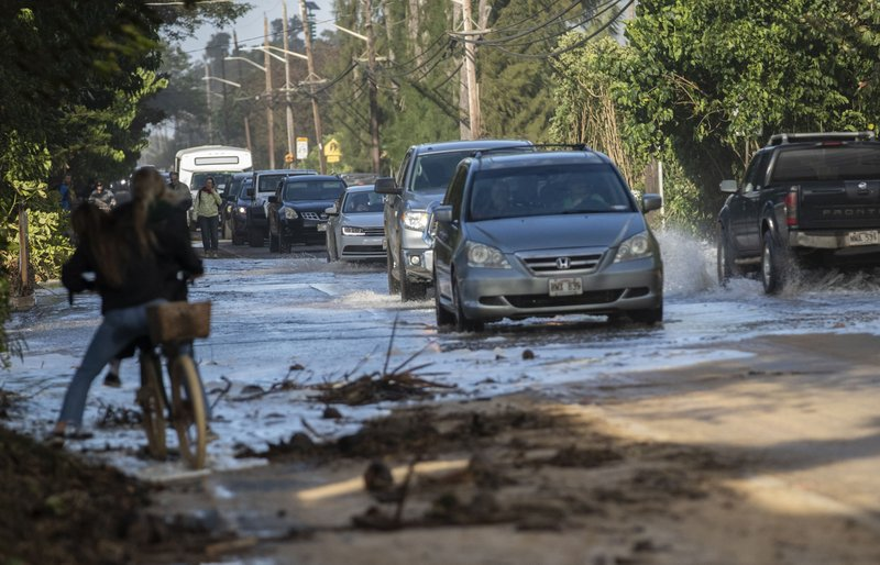FILE - In this Feb. 10, 2019 file photo, vehicles pass through surf that washed over a roadway on Oahu's north shore near Haleiwa, Hawaii. (Cindy Ellen Russel/Honolulu Star-Advertiser via AP, file)
