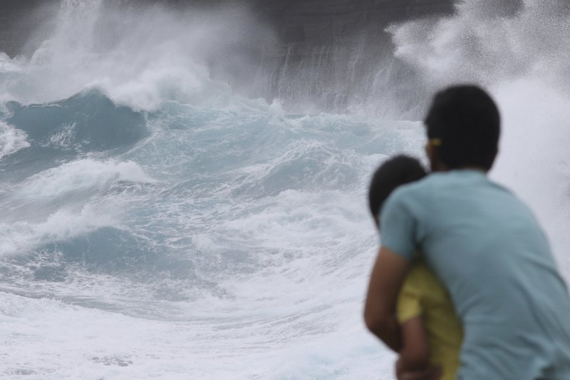 FILE - In this Aug. 24, 2018 file photo, a man and his son watch as waves crash off sea cliffs along the southeast shore of Oahu as Hurricane Lane approaches Honolulu. (AP Photo/Caleb Jones, File)