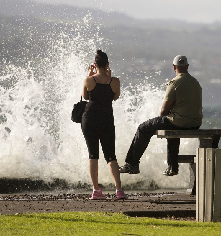 FILE - In this Aug. 31, 2015 file photo, T.J. and Misti Madden, of Hilo, Hawaii, watch as a large wave crashes off a sea wall in Hilo, Hawaii as hurricane Ignacio moves past the state. (AP Photo/Caleb Jones, File)