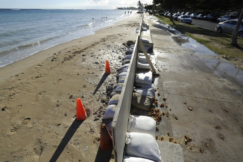 In this June 23, 2017 photo, sand bags line the beach at Ala Moana Beach Park in Honolulu as record high tides hit the islands. (Honolulu Star-Advertiser, Bruce Asato via AP)