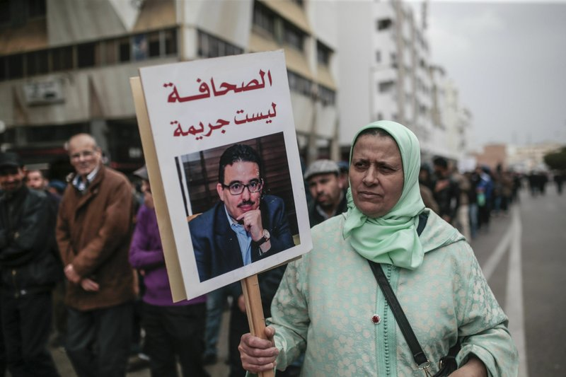 A woman carries a banner of detained journalist Taoufik Bouachrine during a demonstration in Rabat, Morocco, Sunday, April 21, 2019. (AP Photo/Mosa'ab Elshamy)
