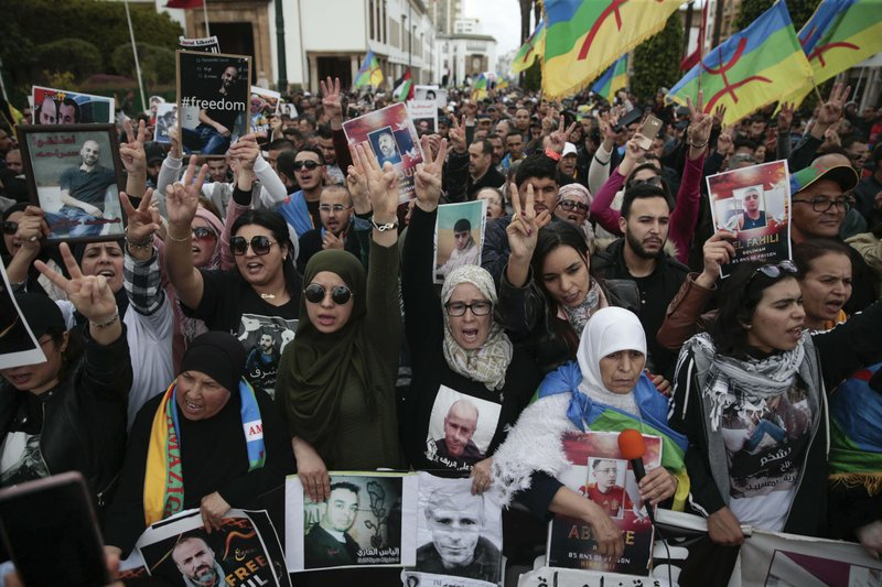 Thousands of Moroccans wave Berber flags and hold photos of detained activists as they take part in a demonstration in Rabat, Morocco, Sunday, April 21, 2019. (AP Photo/Mosa'ab Elshamy)