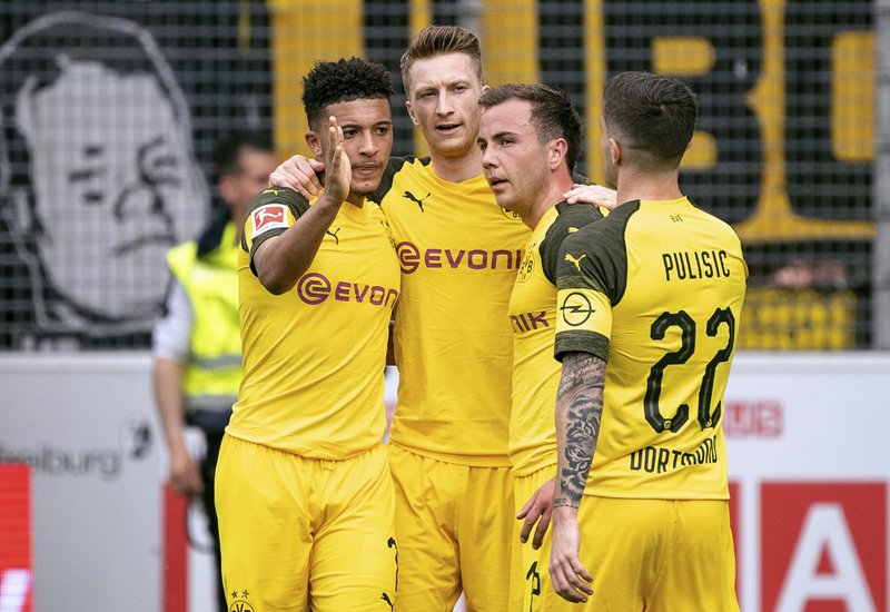Dortmund's Jadon Sancho, Marco Reus, Mario Goetze and Christian Pulisic, from left, celebrate their third goal during the German Bundesliga soccer match between SC Freiburg and Borussia Dortmund in Freiburg, Germany, Sunday, April 21, 2019. (Patrick Seeger/dpa via AP)