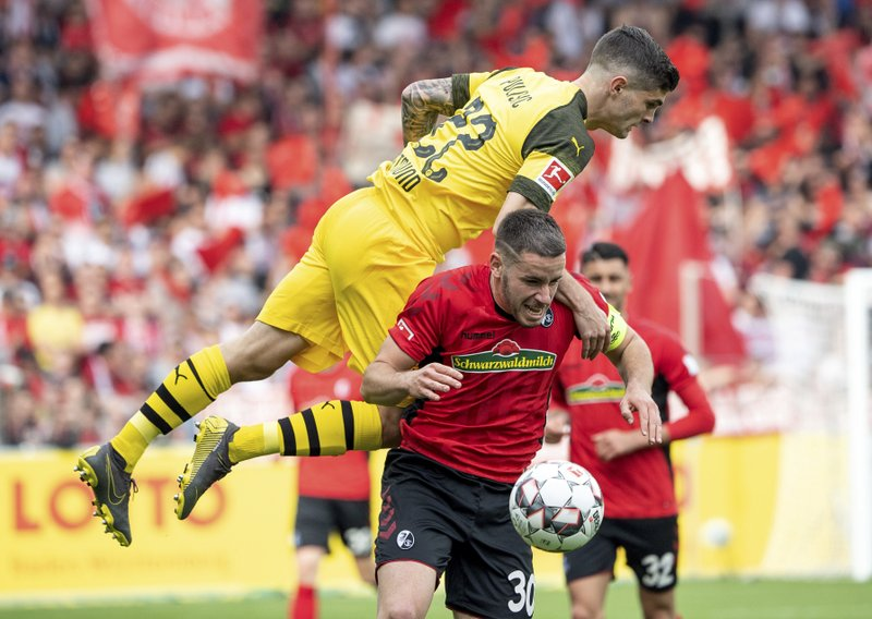Dortmund's Christian Pulisic, up, and Freiburg's Christian Guenter challenge for the ball during the German Bundesliga soccer match between SC Freiburg and Borussia Dortmund in Freiburg, Germany, Sunday, April 21, 2019.  (Patrick Seeger/dpa via AP)