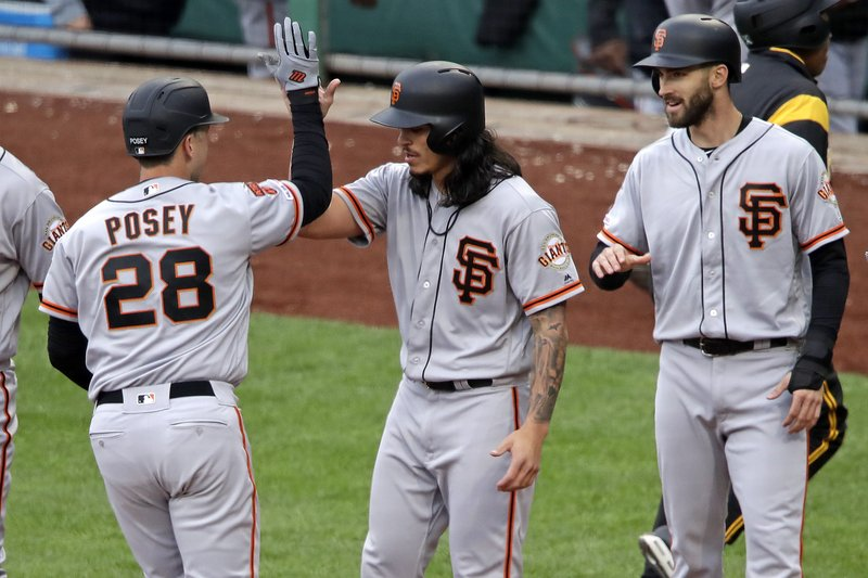 San Francisco Giants' Buster Posey, left, is greeted by Dereck Rodriguez, center, and Steven Duggar, right, as he crosses home plate after hitting a three-run home run off Pittsburgh Pirates starting pitcher Chris Archer in the fifth inning of a baseball game in Pittsburgh, Sunday, April 21, 2019. (AP Photo/Gene J. Puskar)