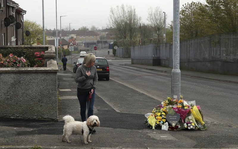 A woman reacts as she stops to pay her respects at the scene Saturday April 20, 2019, in Londonderry, Northern Ireland, where 29-year old journalist Lyra McKee was fatally shot. (Brian Lawless/PA via AP)