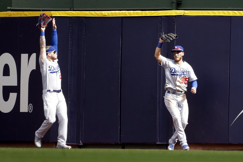 Los Angeles Dodgers' Alex Verdugo, left, reacts after Los Angeles Dodgers' Cody Bellinger, right, makes a catch at the wall during the eighth inning of a baseball game against the Milwaukee Brewers Sunday, April 21, 2019, in Milwaukee. (AP Photo/Aaron Gash)