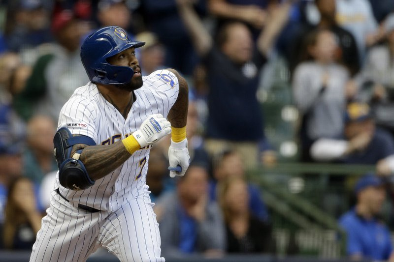 Milwaukee Brewers' Eric Thames watches the ball after hitting a three-run home run during the eighth inning of a baseball game against the Los Angeles Dodgers Sunday, April 21, 2019, in Milwaukee. (AP Photo/Aaron Gash)