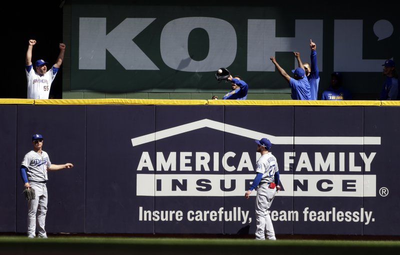 Members of the Milwaukee Brewers' bullpen celebrate in front of Los Angeles Dodgers' Joc Pederson and Alex Verdugo (27) after a home run hit by Milwaukee Brewers' Lorenzo Cain during the fifth inning of a baseball game Sunday, April 21, 2019, in Milwaukee. (AP Photo/Aaron Gash)
