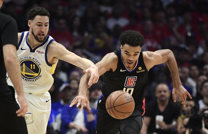 Golden State Warriors guard Klay Thompson, left, and Los Angeles Clippers guard Jerome Robinson reach for a loose ball during the first half in Game 4 of a first-round NBA basketball playoff series Sunday, April 21, 2019, in Los Angeles. (AP Photo/Mark J. Terrill)