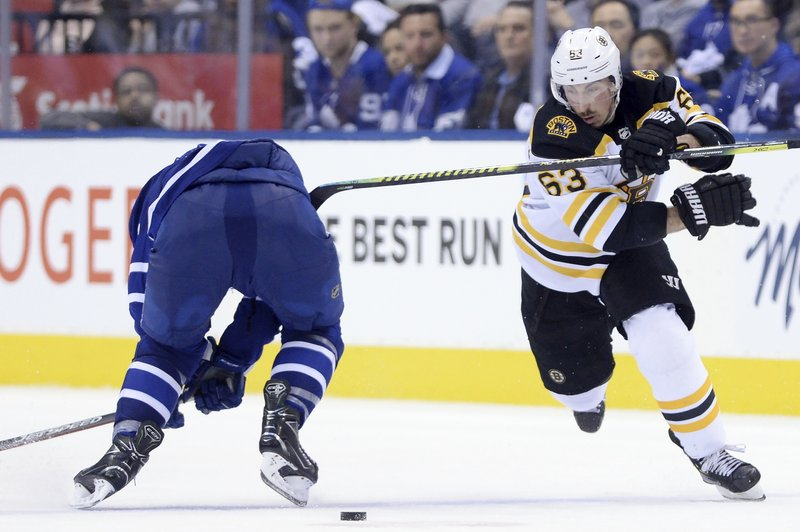 Boston Bruins left wing Brad Marchand (63) skates around Toronto Maple Leafs defenseman Morgan Rielly (44) ahead of scoring an empty net goal during the third period of Game 6 of an NHL hockey first-round playoff series Sunday, April 21, 2019, in Toronto. (Nathan Denette/The Canadian Press via AP)