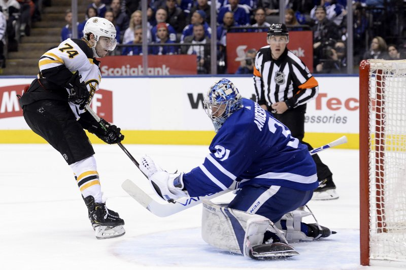 Toronto Maple Leafs goaltender Frederik Andersen (31) makes a glove save against Boston Bruins left wing Jake DeBrusk (74) on a breakaway during the third period of Game 6 of an NHL hockey first-round playoff series Sunday, April 21, 2019, in Toronto. (Nathan Denette/The Canadian Press via AP)