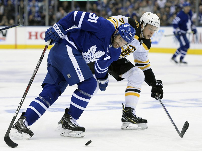 Toronto Maple Leafs center John Tavares (91) battles for the puck with Boston Bruins defenseman Charlie McAvoy (73) during the second period of Game 6 of an NHL hockey first-round playoff series Sunday, April 21, 2019, in Toronto. (Nathan Denette/The Canadian Press via AP)