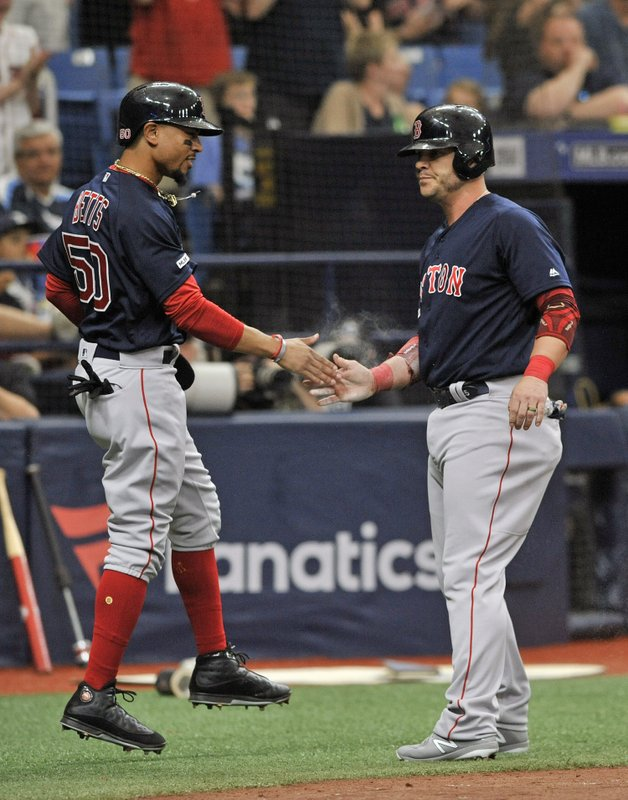Boston Red Sox's Mookie Betts, left, and Steve Pearce celebrate after scoring on Xander Bogaerts' two-run single off Tampa Bay Rays reliever Chaz Roe during the sixth inning of a baseball game Sunday, April 21, 2019, in St. (AP Photo/Steve Nesius)