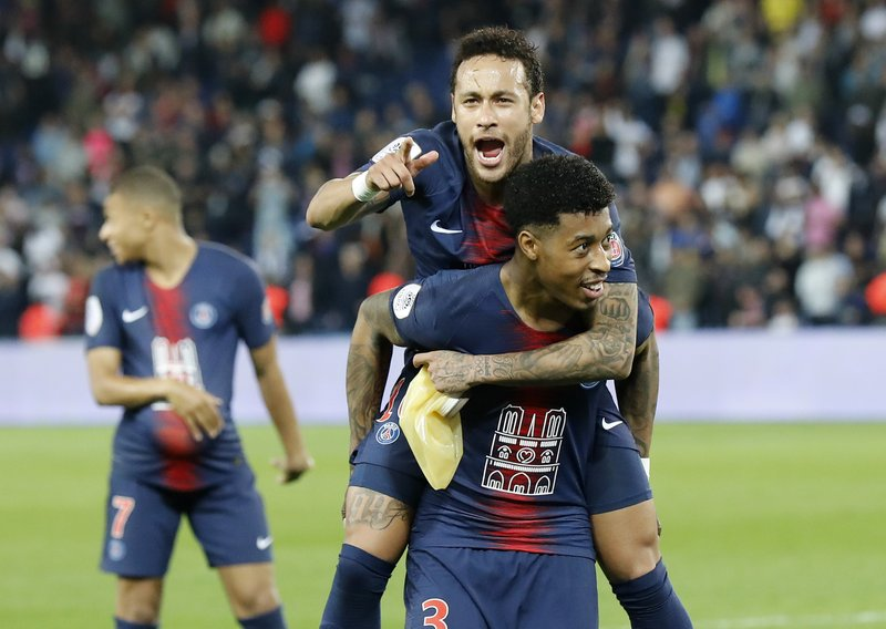 PSG's Neymar, top, sits on the back of PSG's Presnel Kimpembe after the French League One soccer match between Paris-Saint-Germain and Monaco at the Parc des Princes stadium in Paris, Sunday April 21, 2019. (AP Photo/Michel Euler)