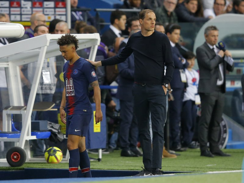 PSG's Thilo Kehrer, left, is patted on the back by PSG's coach Thomas Tuchel as he leaves the field during the French League One soccer match between Paris-Saint-Germain and Monaco at the Parc des Princes stadium in Paris, Sunday April 21, 2019. (AP Photo/Michel Euler)
