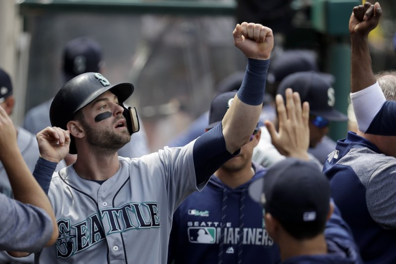 Seattle Mariners' Mitch Haniger celebrates in the dugout after scoring on single during the third inning of a baseball game against the Los Angeles Angels in Anaheim, Calif. (AP Photo/Chris Carlson)