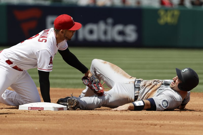 Los Angeles Angels shortstop Andrelton Simmons, left, tags out Seattle Mariners' Tom Murphy during a rundown during the second inning of a baseball game in Anaheim, Calif. (AP Photo/Chris Carlson)