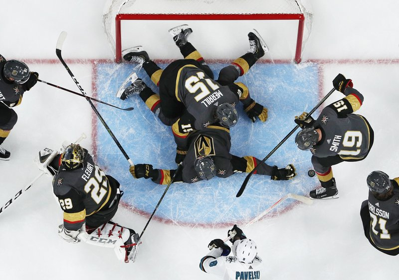 Vegas Golden Knights defenseman Jon Merrill (15) and defenseman Colin Miller (6) help keep the puck out of the net against the San Jose Sharks during the first overtime in Game 6 of a first-round NHL hockey playoff series Sunday, April 21, 2019, in Las Vegas. (AP Photo/John Locher)