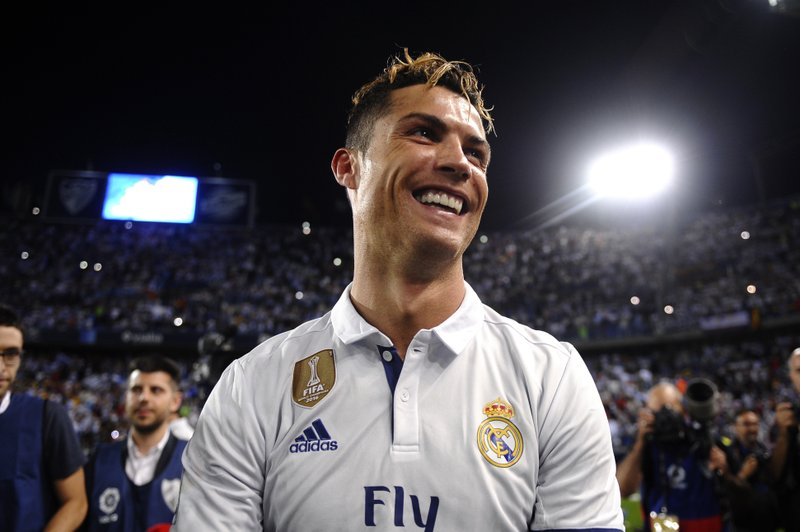 FILE - In this Sunday, May 21, 2017 file photo, Real Madrid's Cristiano Ronaldo celebrates after winning the Spanish La Liga title at the end of the soccer match between Malaga and Real Madrid in Malaga, Spain. (with Manchester United), the Spanish league (with Madrid) and Serie A. (AP Photo/Daniel Tejedor, File)