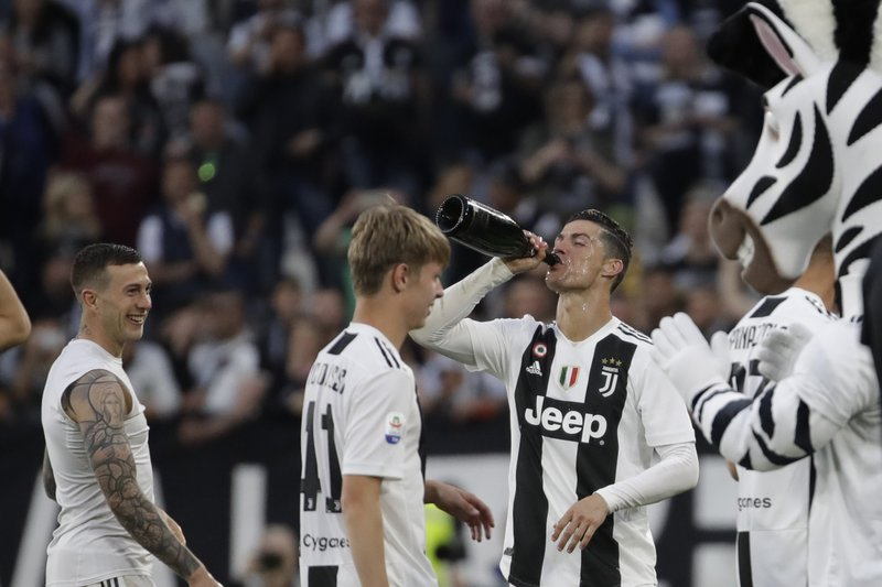 Juventus' Cristiano Ronaldo, right, celebrates with his teammates at the end of a Serie A soccer match between Juventus and AC Fiorentina, at the Allianz stadium in Turin, Italy, Saturday, April 20, 2019. (AP Photo/Luca Bruno)