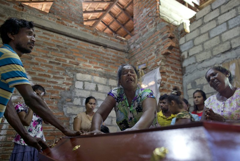 Lalitha, center, weeps over the coffin with the remains of 12-year old niece, Sneha Savindi, who was a victim of Easter Sunday bombing at St. (AP Photo/Gemunu Amarasinghe)