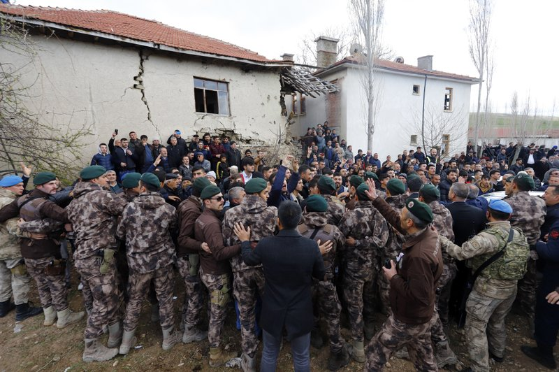 Security officials try to stop protesters attacking Kemal Kilicdaroglu, the leader of Turkey's main opposition Republican People's Party, during the funeral of a soldier who was slain during clashes with Kurdish rebels at Iraq border, outside Ankara, Turkey, Sunday, April 21, 2019. (DHA via AP)