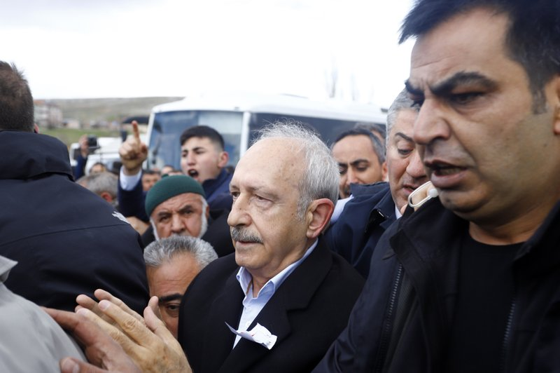 Bodyguards protect Kemal Kilicdaroglu, the leader of Turkey's main opposition Republican People's Party, as protesters attack during the funeral of a soldier who was slain during clashes with Kurdish rebels at Iraq border, outside Ankara, Turkey, Sunday, April 21, 2019. (DHA via AP Photo)