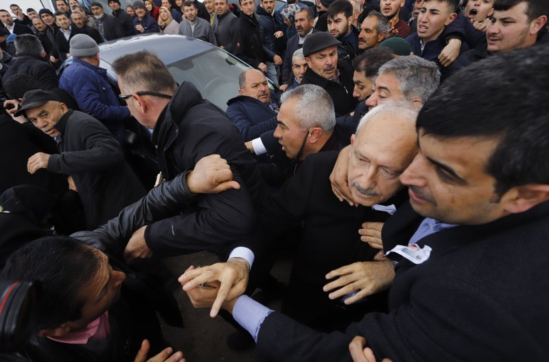 Bodyguards protect Kemal Kilicdaroglu, the leader of Turkey's main opposition Republican People's Party, as a man throws a punch toward him, during the funeral of a soldier who was slain during clashes with Kurdish rebels at Iraq border, outside Ankara, Turkey, Sunday, April 21, 201. (DHA via AP Photo)