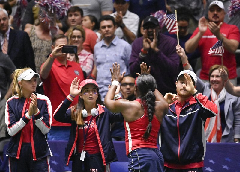 United States' Sloane Stephens, front, high-fives fans after beating Switzerland's Viktorija Golubic during their playoff-round Fed Cup tennis match, Sunday, April 21, 2019, in San Antonio. (AP Photo/Darren Abate)