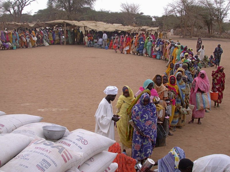FILE - In this July 2004 file photo, displaced Sudanese women line up to receive food at Kasab Internally Displaced People's camp near Kutum, Northern Darfur, Sudan. (AP Photo/Marcus Prior/WFP, File)