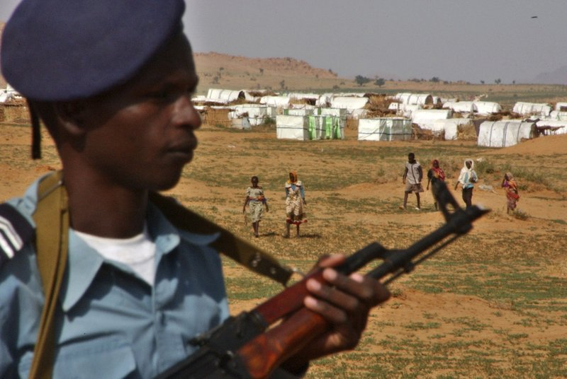 FILE - In this Aug. 25, 2004 file photo, a Sudanese policeman stands guard at Abu Shouk camp, in North Darfur, Sudan, where more than 40 thousand displaced people receive food and shelter from international aid agencies. (AP Photo/Amr Nabil, File)