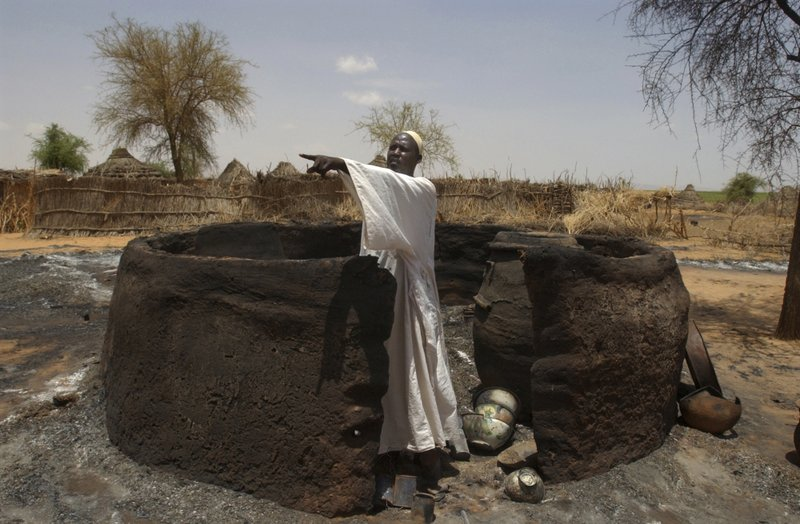 FILE - In this Aug. 29, 2004 file photo, Adam Salim Abu Bakir, a Sudanese villager from Um Hashab village, in North Darfur province, points to his burned hut. (AP Photo/Amr Nabil, File)