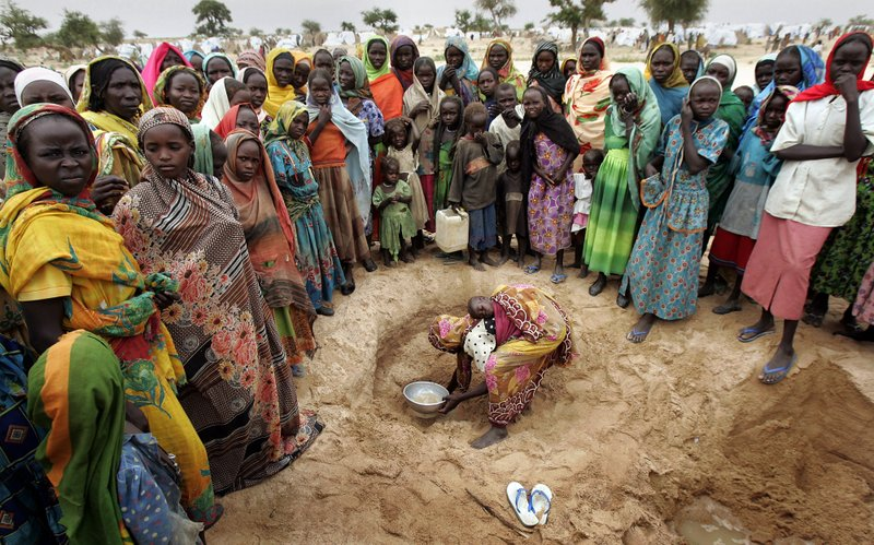 FILE - In this Sept. 27, 2004 file photo, a woman digs for water in a wadi (dry riverbed) at a makeshift camp for internally displaced people near Seleah village in Sudan's West Darfur province. (AP Photo/Ben Curtis, File)