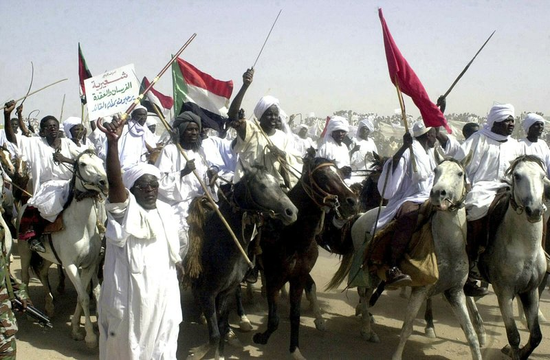 FILE - In this May 19, 2004 file photo, Arab and African horsemen from Sudan's Shairia locality parade before then Sudanese President Omar Al-Bashir, as a show of solidarity in Nyala, capital of the country's southern Darfur state. (AP Photo/Abd Raouf, File)