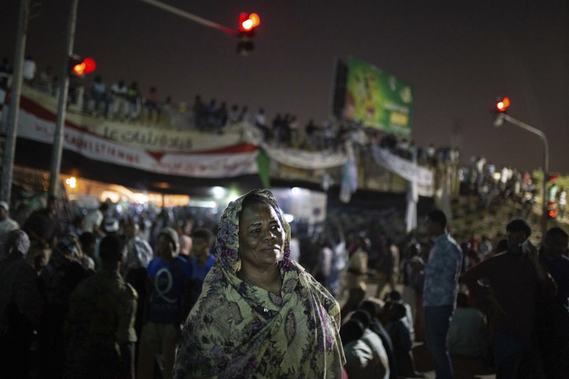 In this Thursday, April 18, 2019 photo, Amal al-Zein, an activist who was detained under former Sudanese President Omar al-Bashir, attends a protest in Khartoum, Sudan. (AP Photos/Salih Basheer)